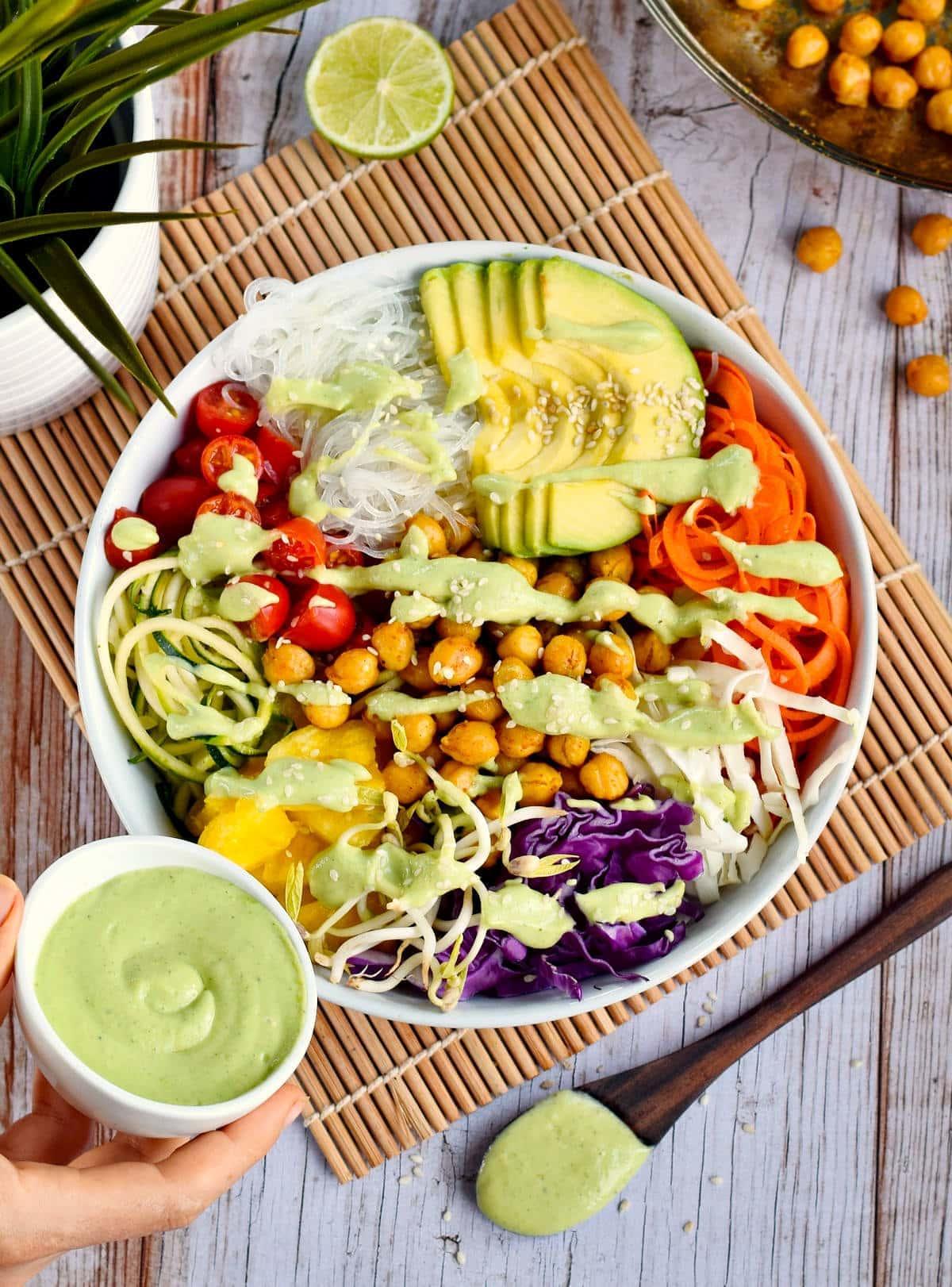 hand pouring green avocado dressing over vegan buddha bowl with chickpeas
