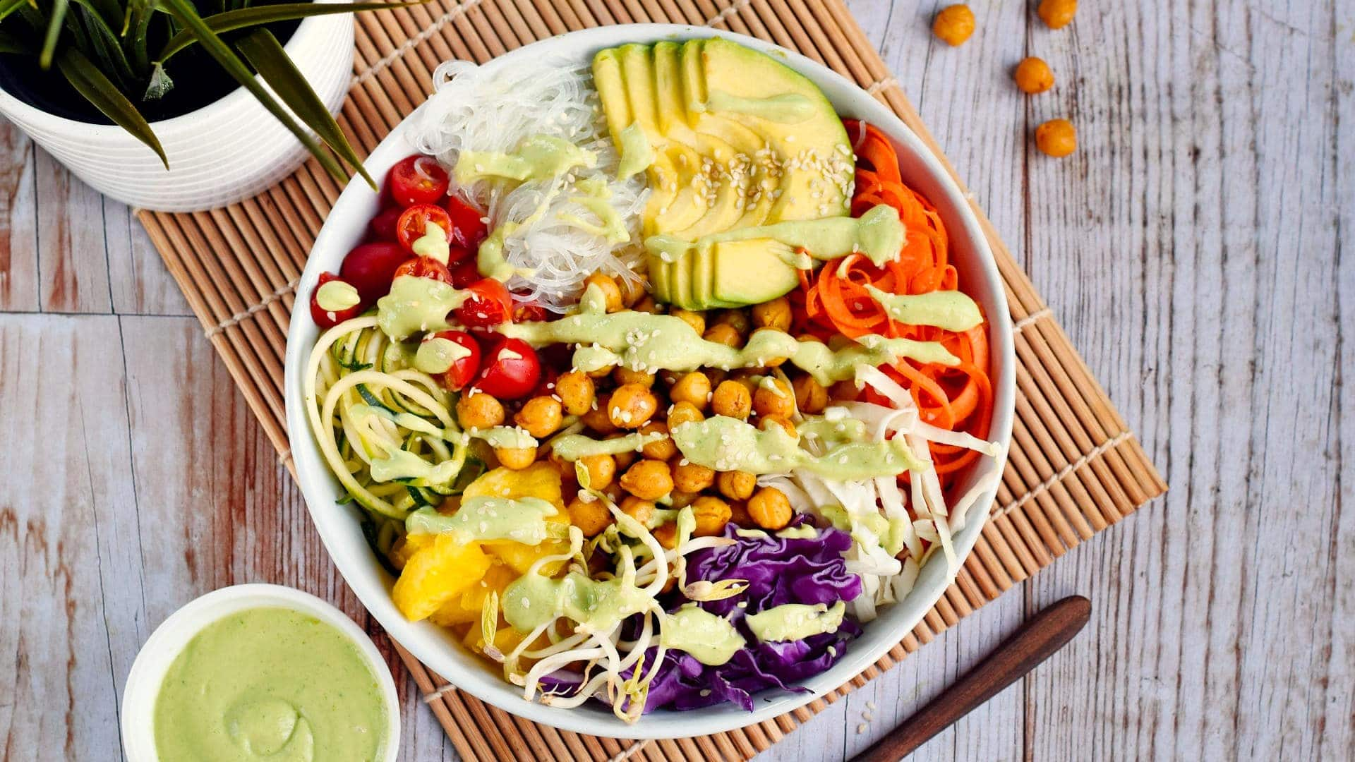 healthy salad with chickpeas avocado colorful veggies and green dressing on the side
