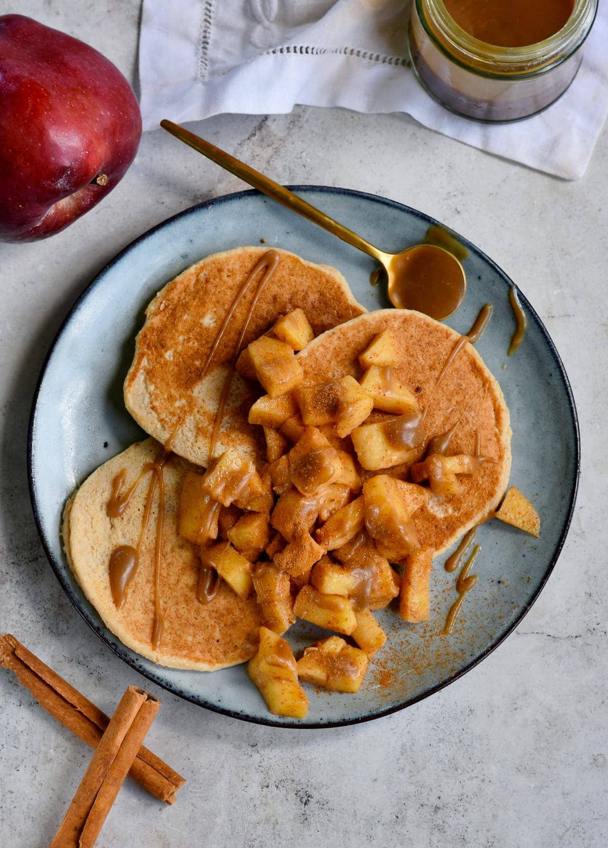 pancakes on plate with apples and caramel sauce