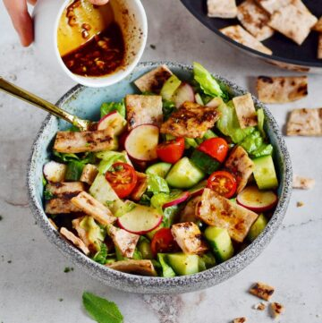 pouring olive oil dressing over fattoush salad