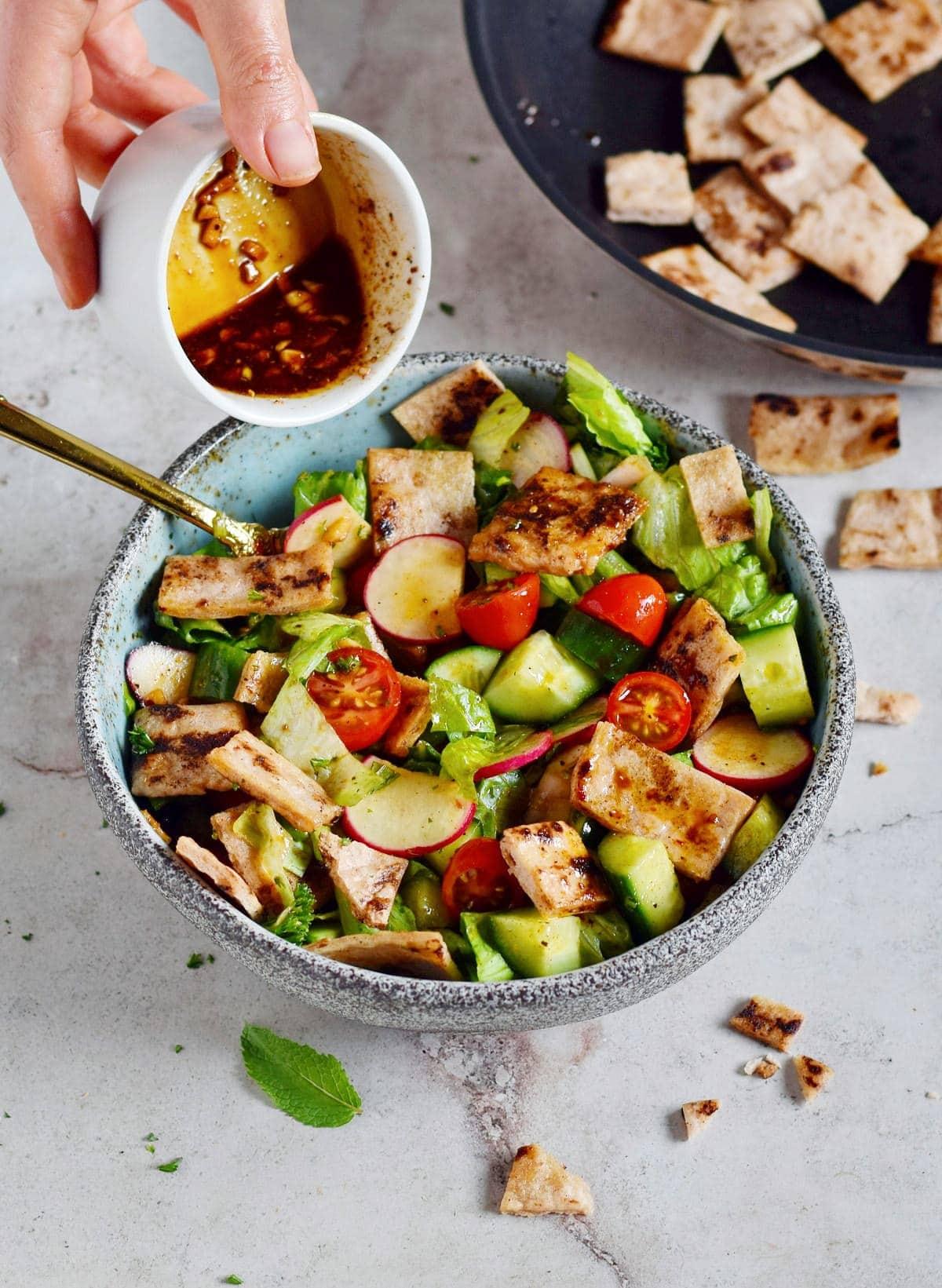 Olivenöl-Dressing wird über Fattoush-Salat gegossen.