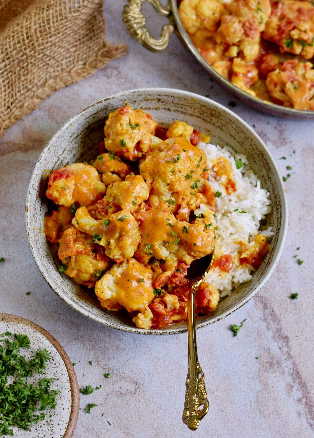 roasted cauliflower curry in bowl with rice and spoon