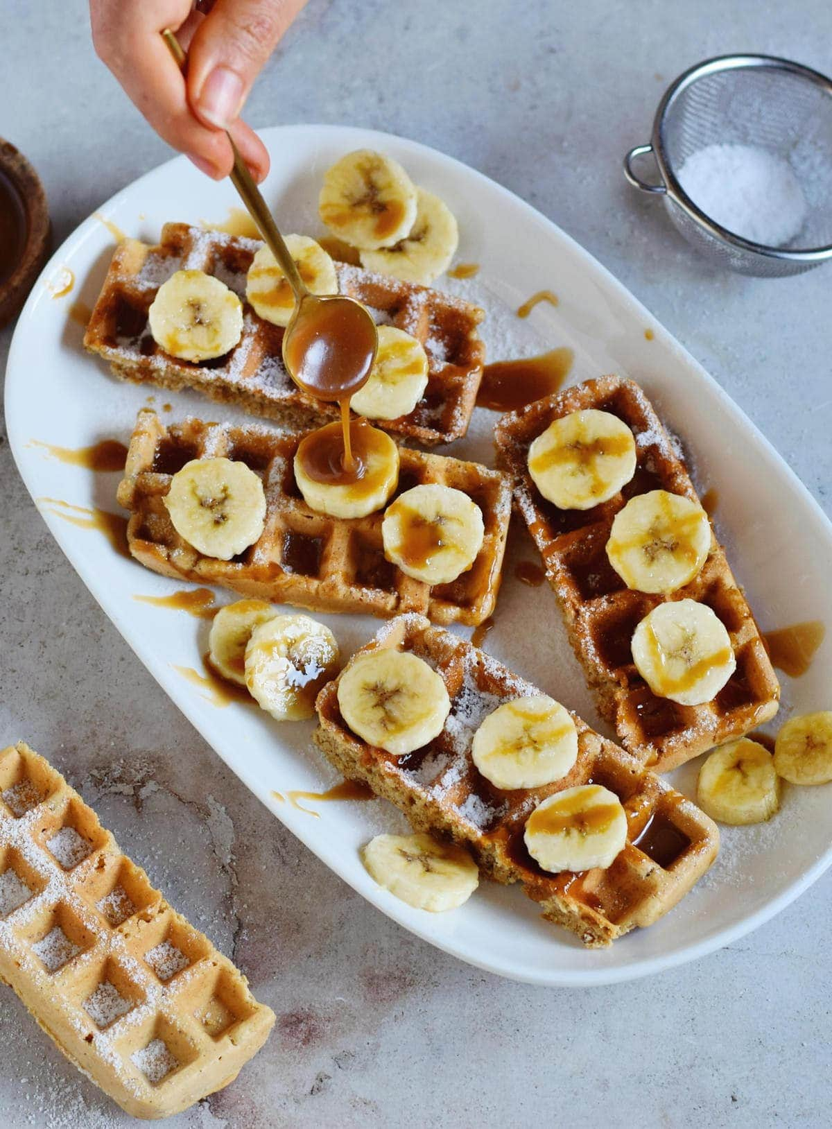 waffles on a plate with bananas and caramel sauce