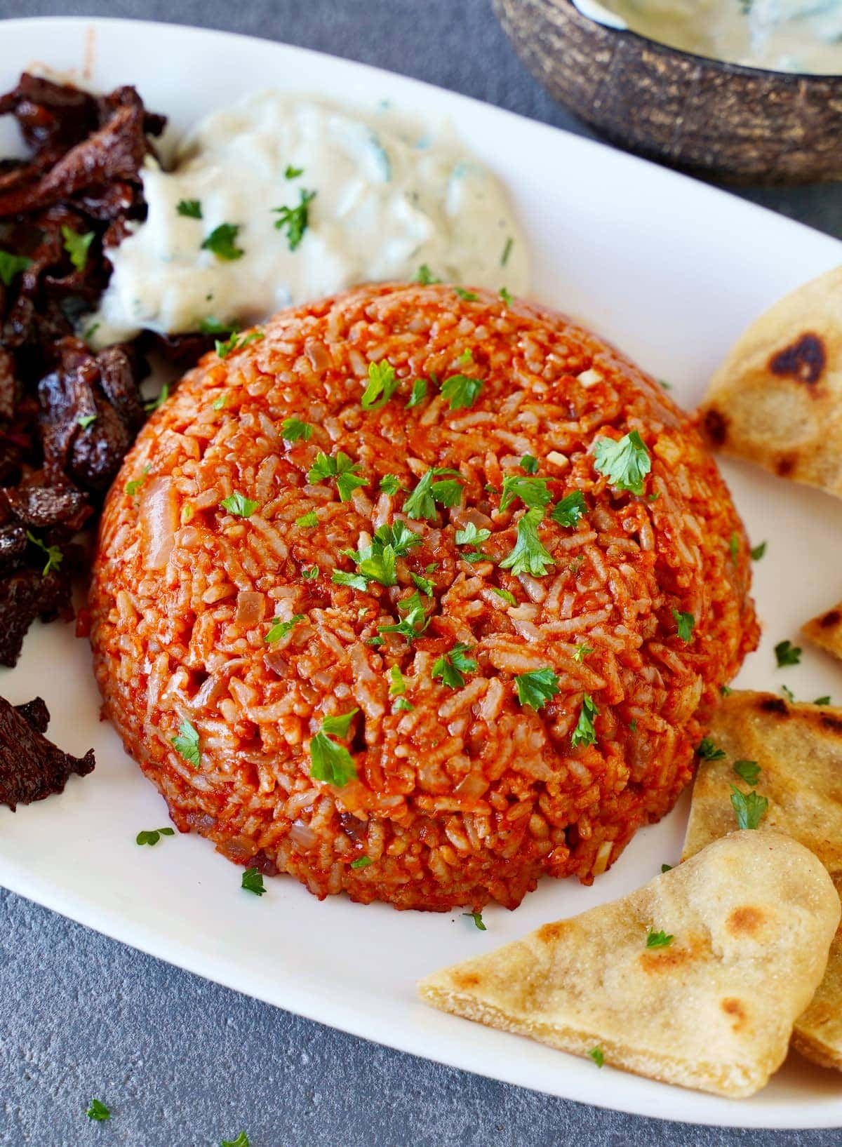 Greek tomato rice with vegan gyro tzatziki and pita chips on white plate