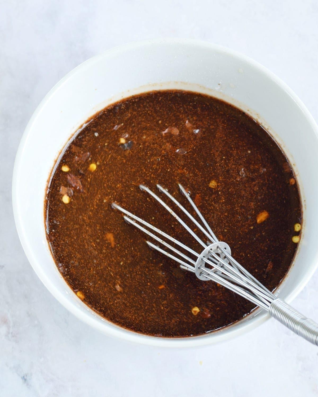 braune Sauce in weißer Schüssel mit Schneebesen