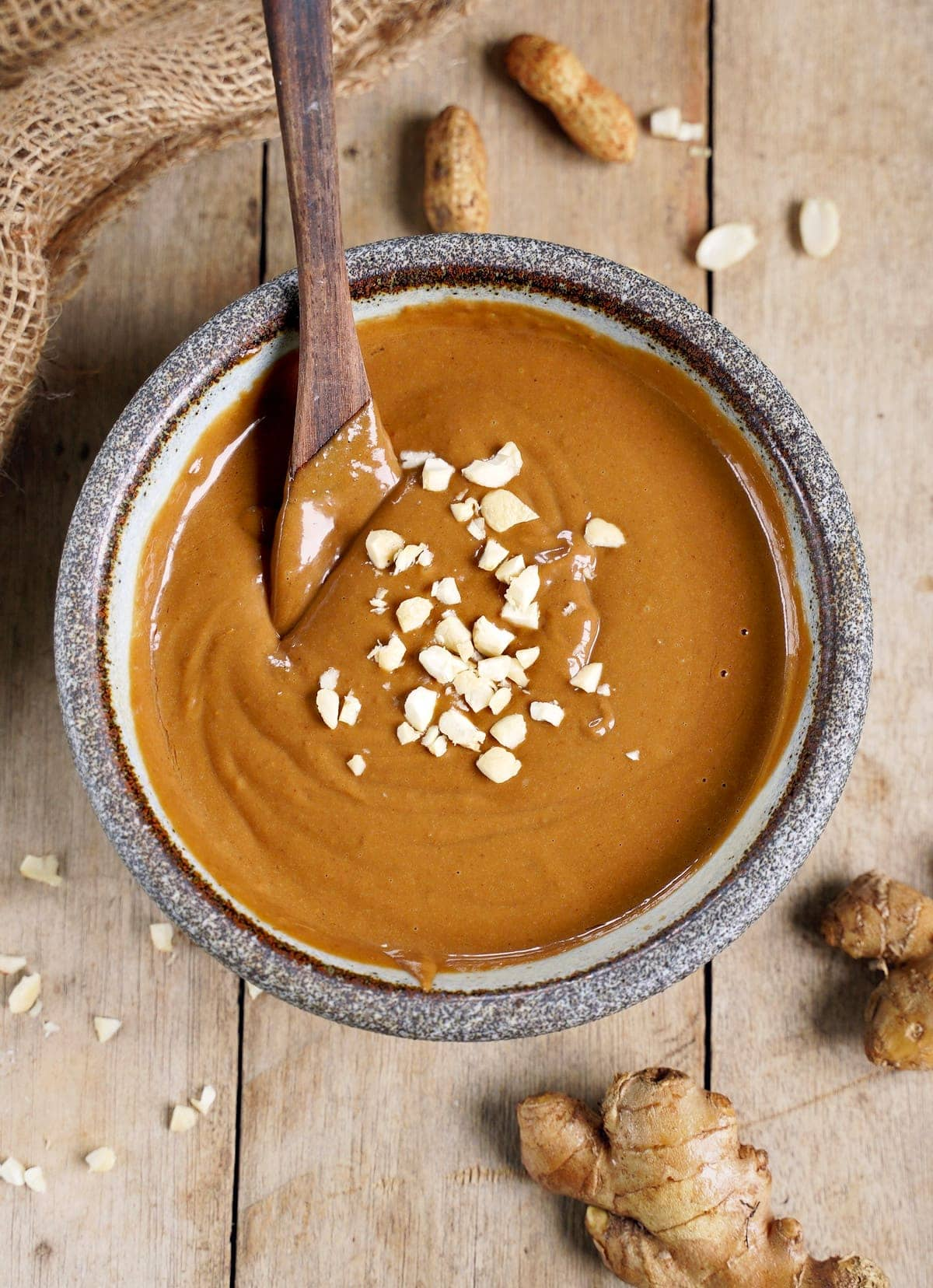 brown sauce with peanuts in bowl with wooden spoon