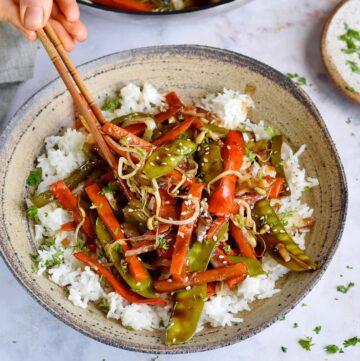 eating vegan chop suey over rice with chopsticks