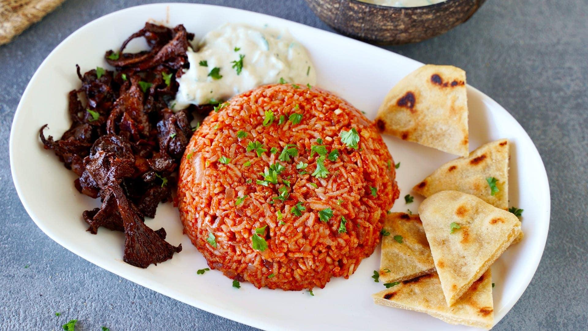 horizontal shot of tomato rice with vegan gyro and pita chips