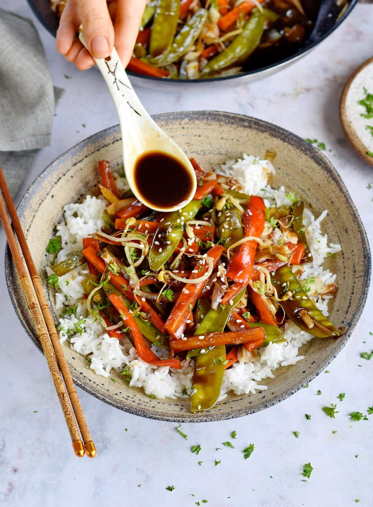pouring brown sauce over vegetable chop suey