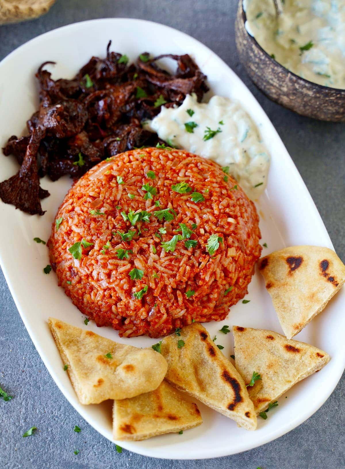 gyro and pita on white plate with tzatziki and pilaf