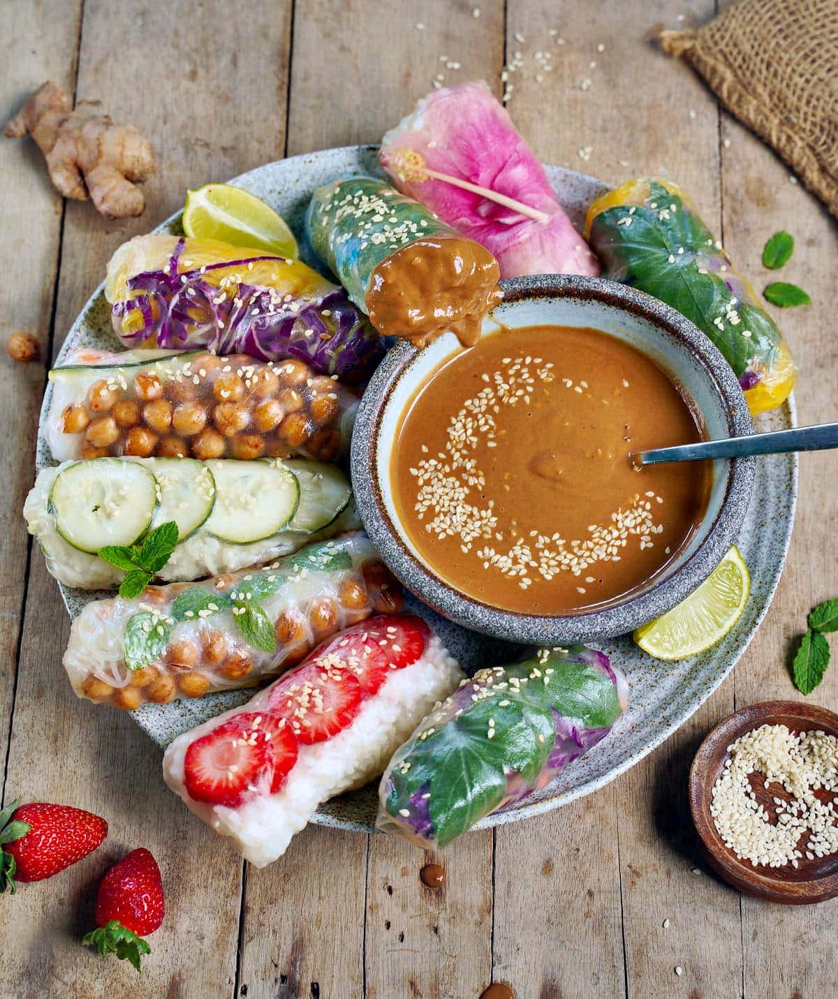 summer roll dipped in peanut sauce on large plate