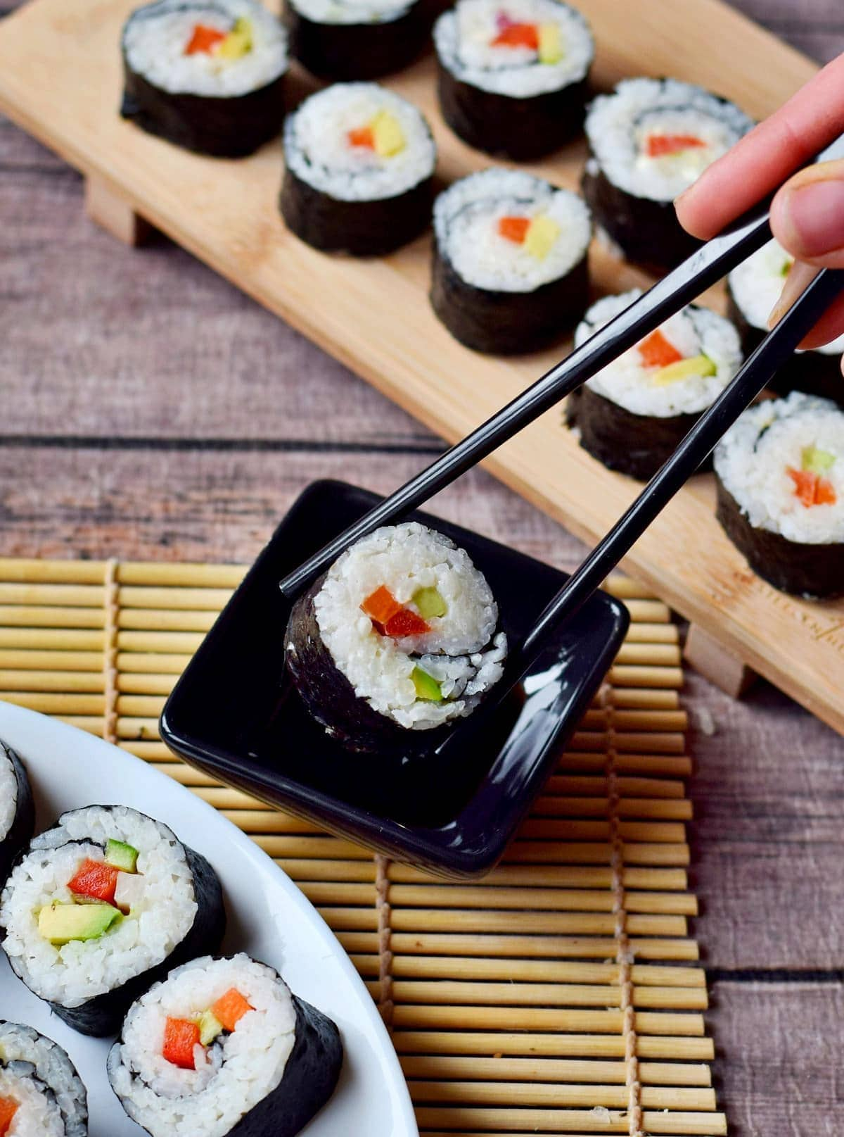 vegetarian sushi roll dipped in soy sauce with chopsticks