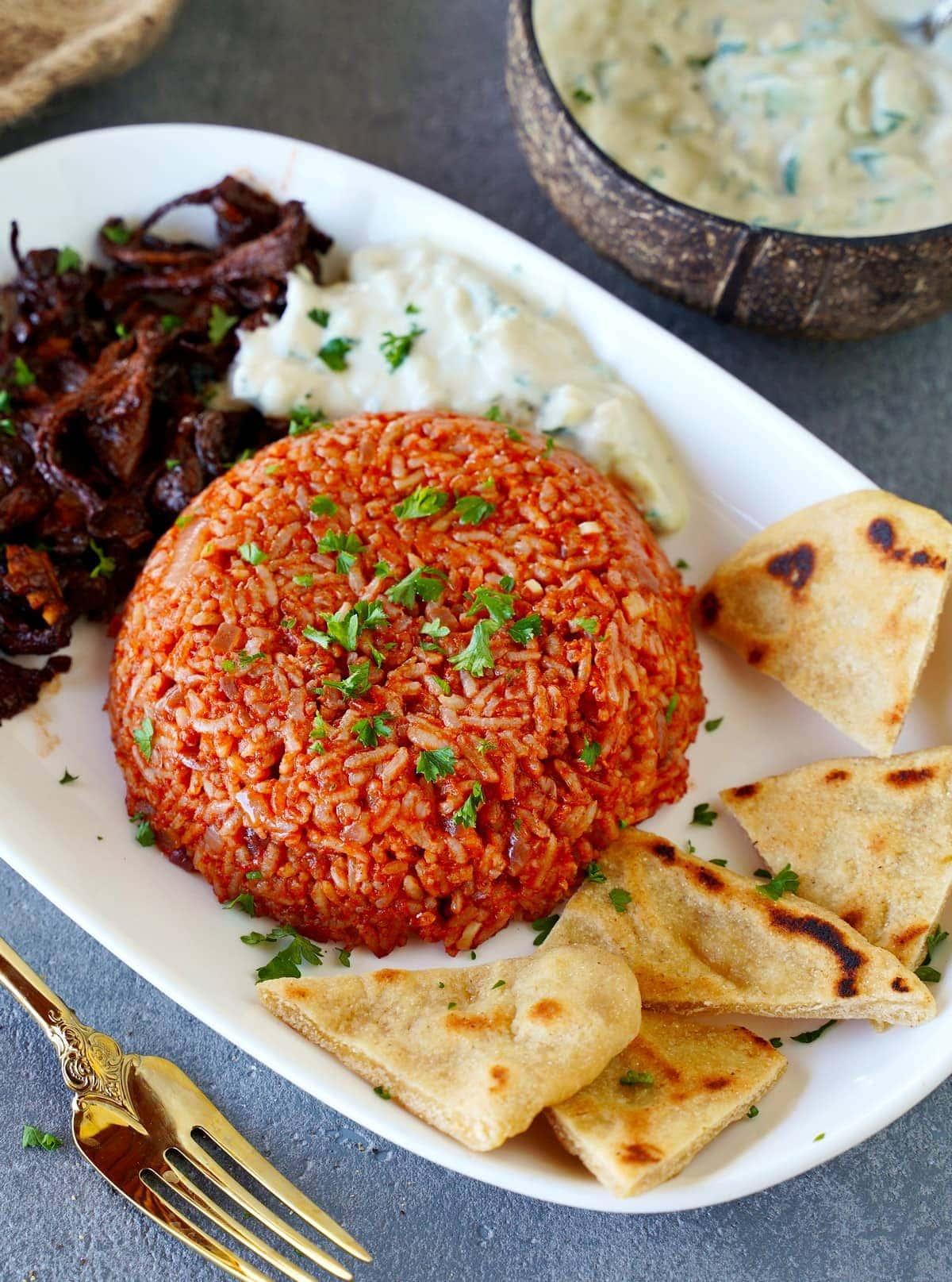 tomato rice with pita gyro and tzatziki on white plate