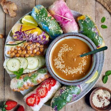 vegan summer rolls on large plate with peanut sauce in the middle