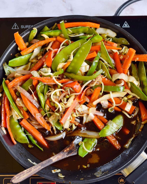 Gemüse mit brauner Sauce in einer schwarzen Pfanne
