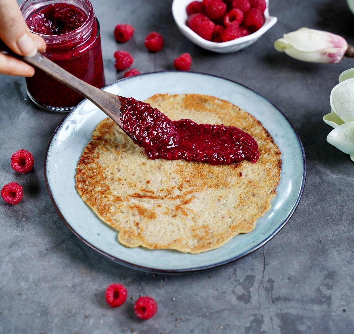 a crepe on a plate with homemade jelly made from rasperries