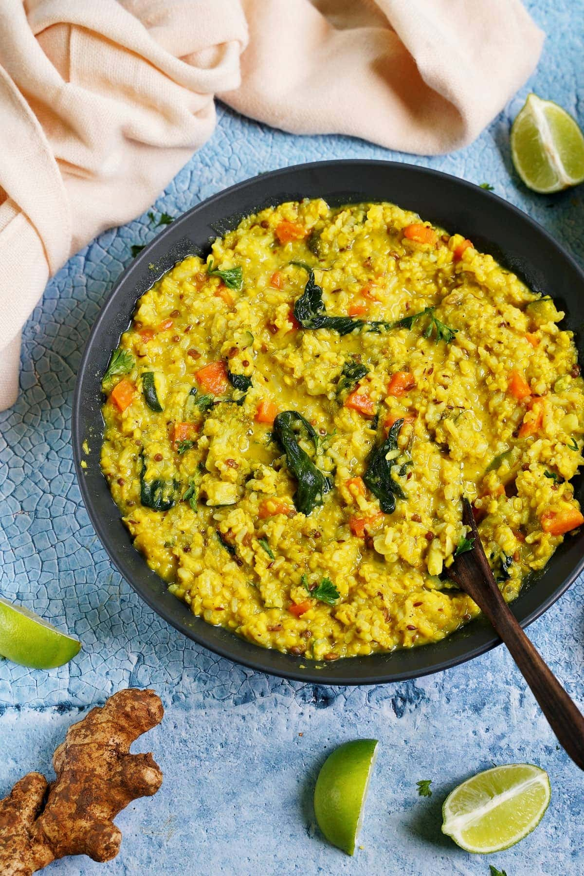 ayurvedic moong dal dish in black bowl with wooden spoon