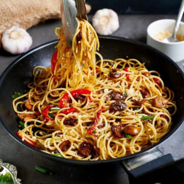 garlic noodles in black skillet with veggies and tongs