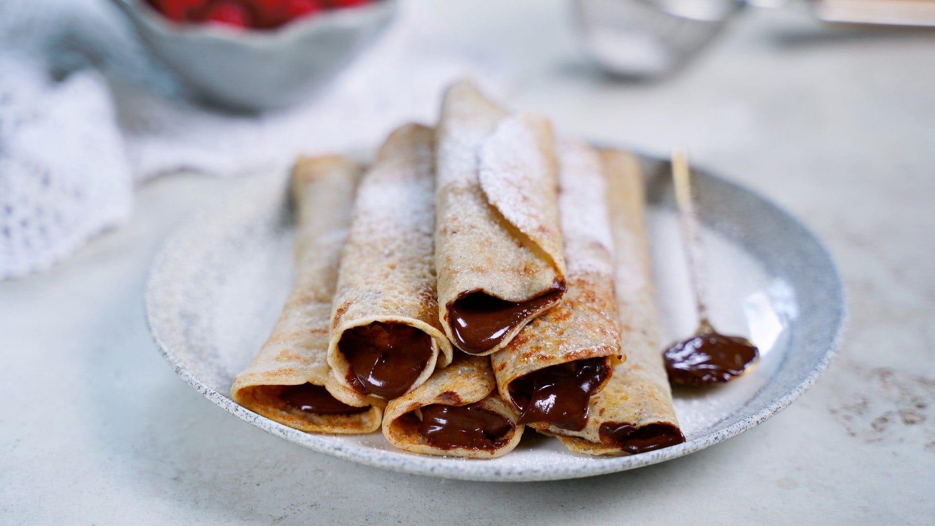 Queraufnahme von 6 Crêpes mit Schokoladen-Aufstrich auf einem Teller