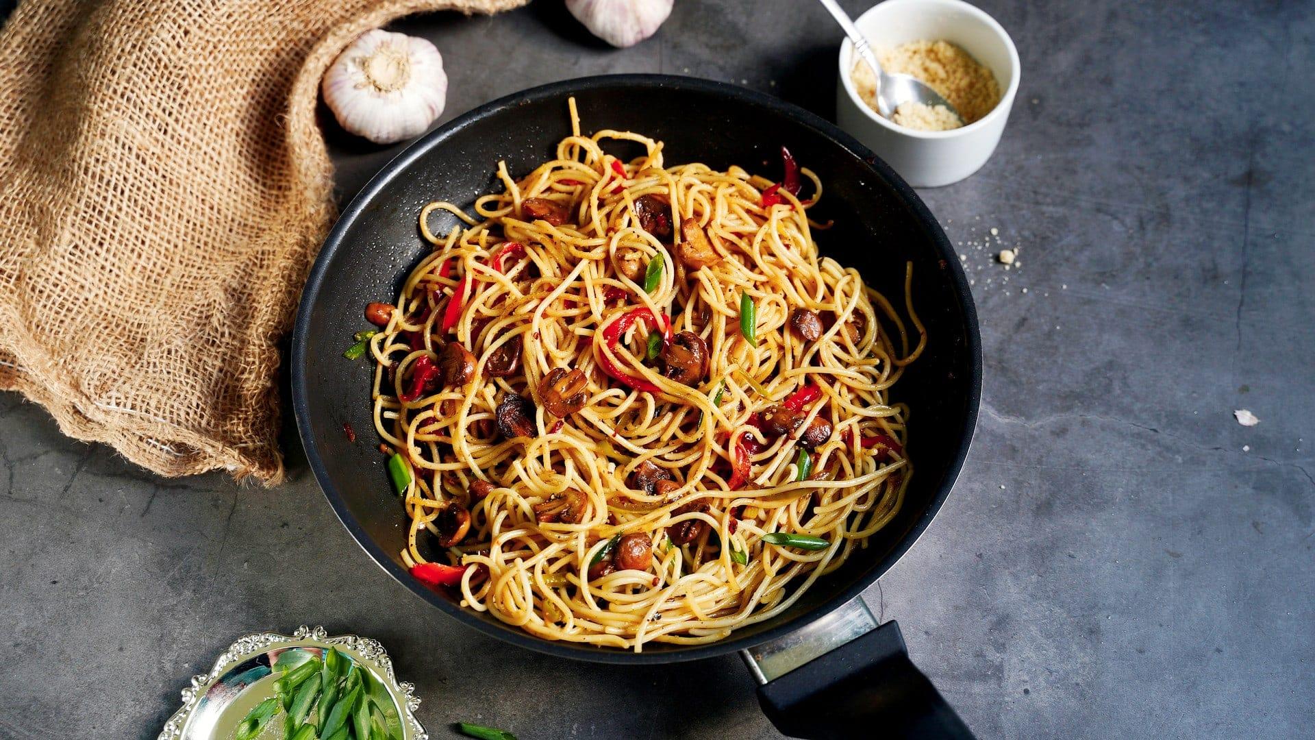 horizontal shot of garlic noodles with veggies in black pan