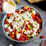 pouring creamy tahini dressing over kidney bean salad