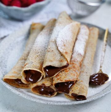 stack of 6 gluten-free crepes filled with vegan Nutella on plate with raspberries in the background