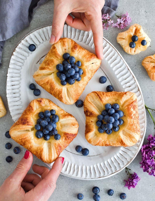 3 Blätterteig Puddingplunder mit Blaubeeren auf einem Teller