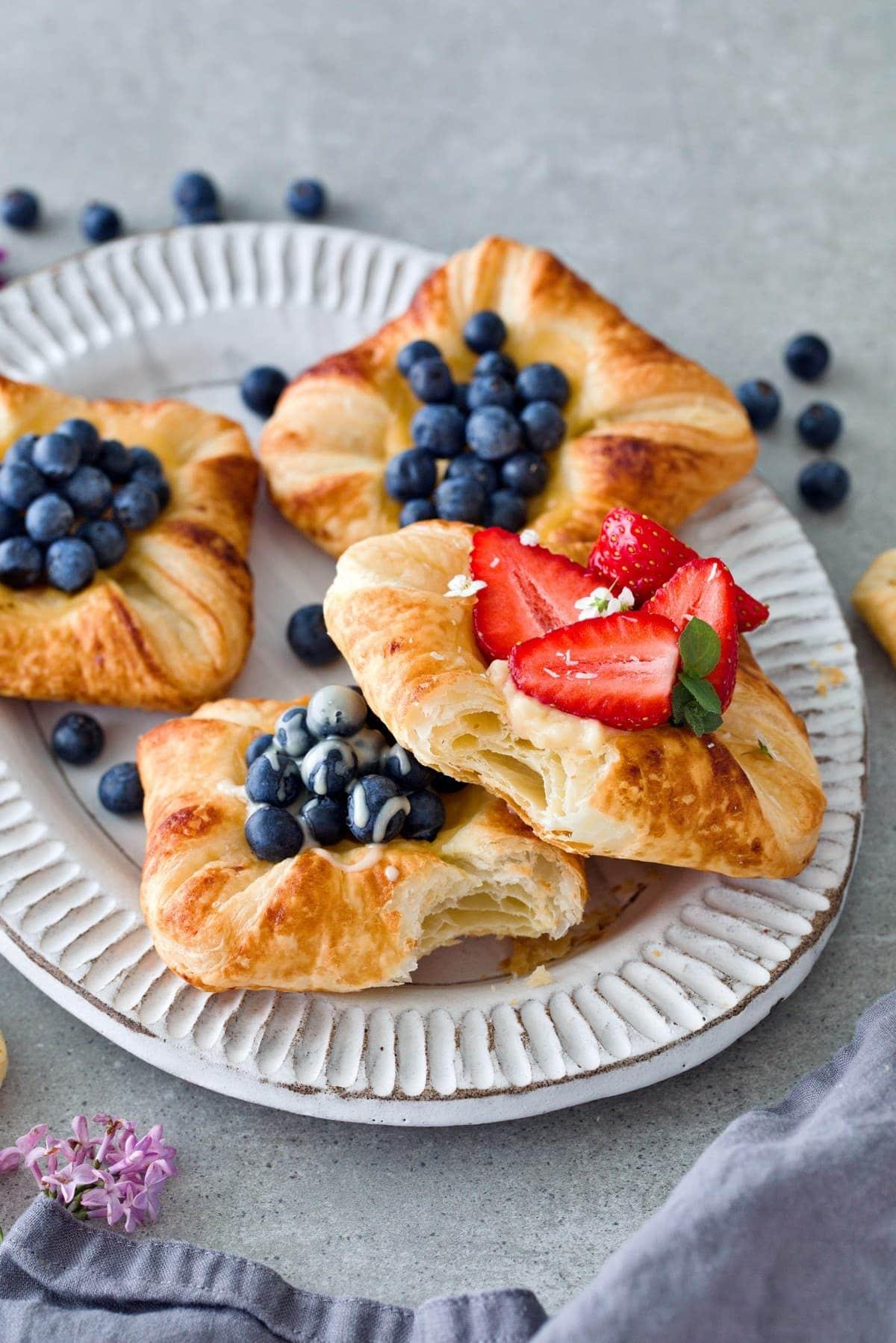 4 Blätterteigteilchen (Plunder) mit Blaubeeren und Erdbeeren auf einem Teller