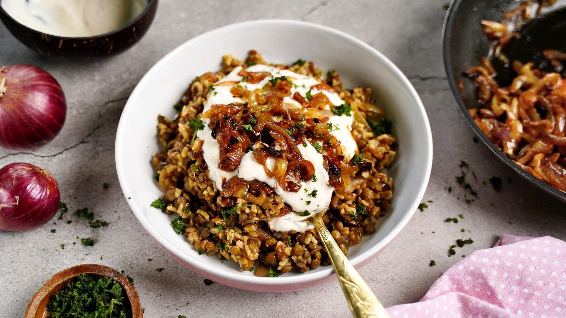 Libanesische Linsen und Reis in Schale mit karamellisierten Zwiebeln und veganem Joghurt