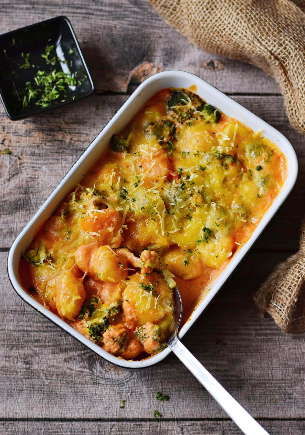 baked gnocchi with broccoli and vegan cheese from above with ladle