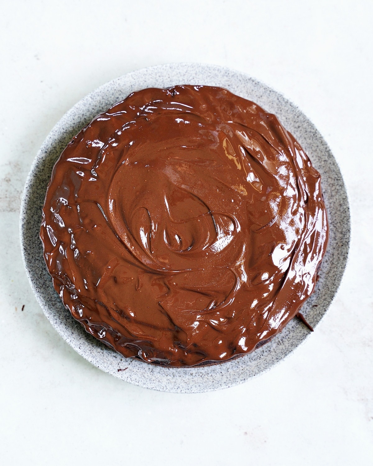 chocolate cake with ganache on plate from above