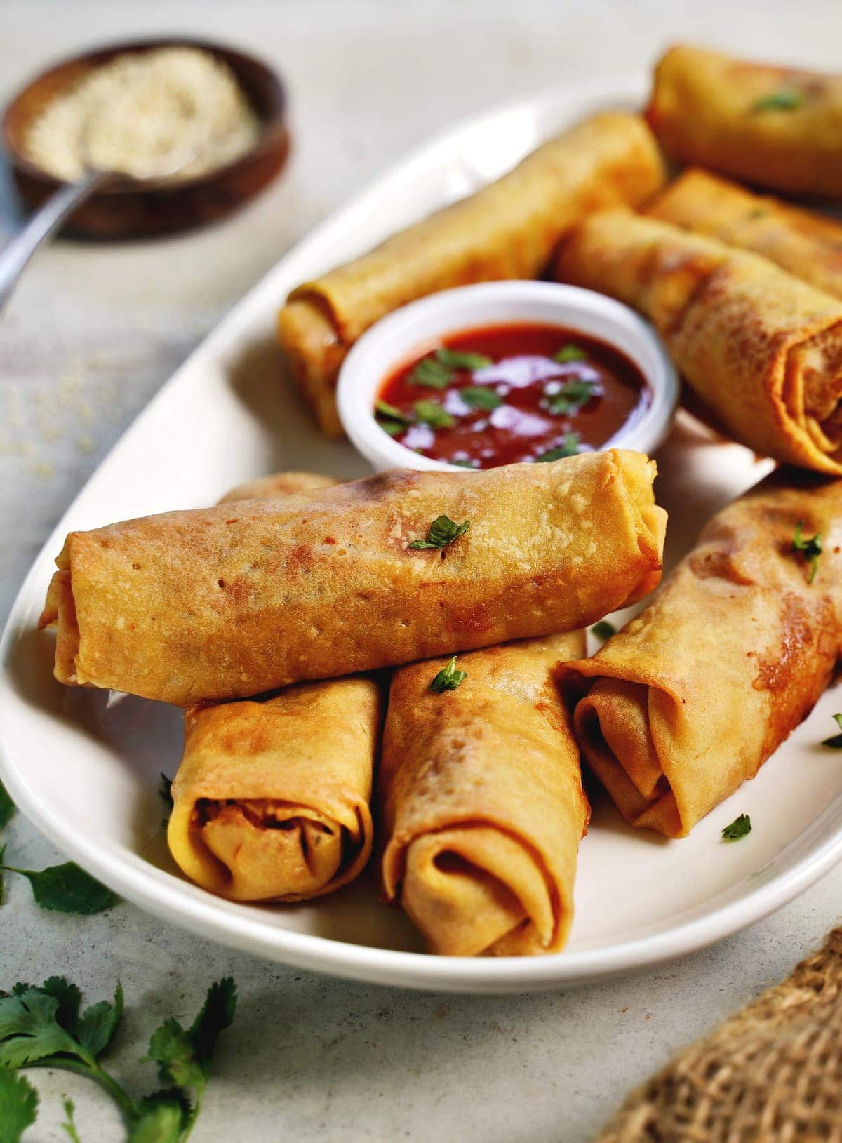 close-up of baked gluten-free spring rolls on white plate
