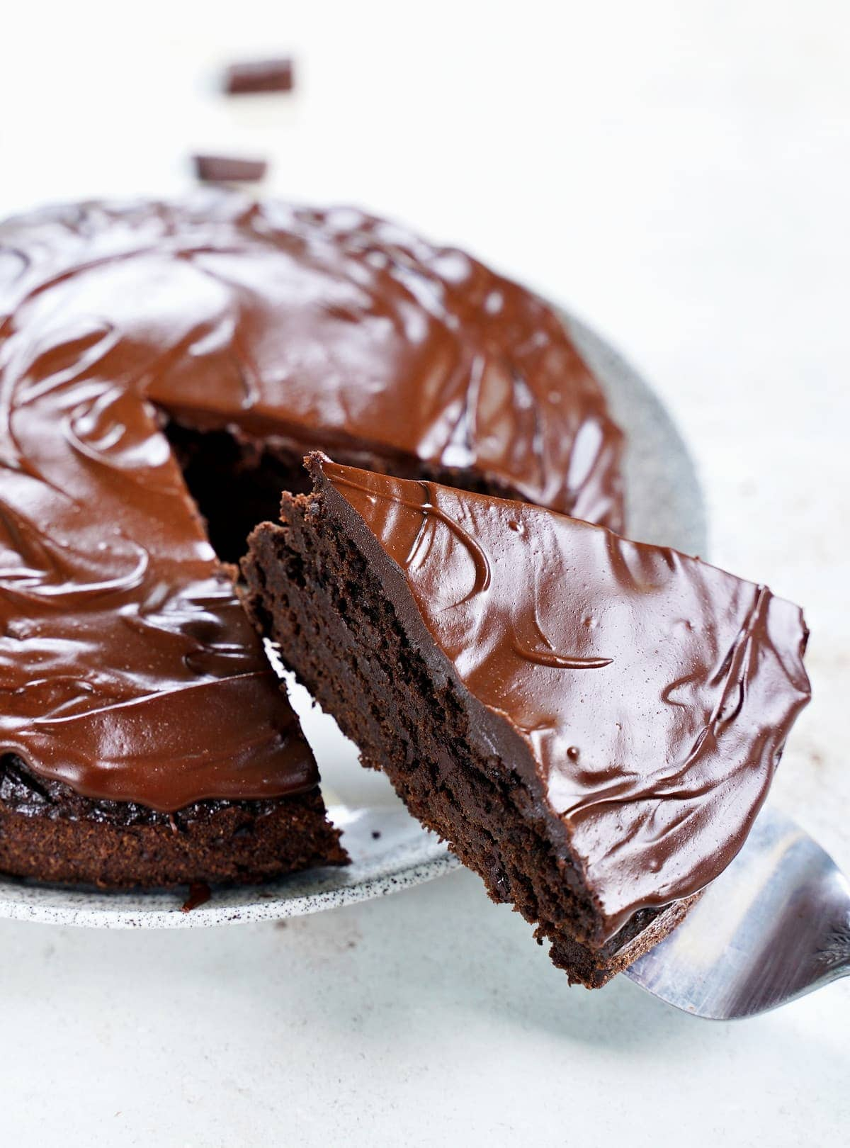 close-up of vegan chocolate cake with ganache and a piece cut out