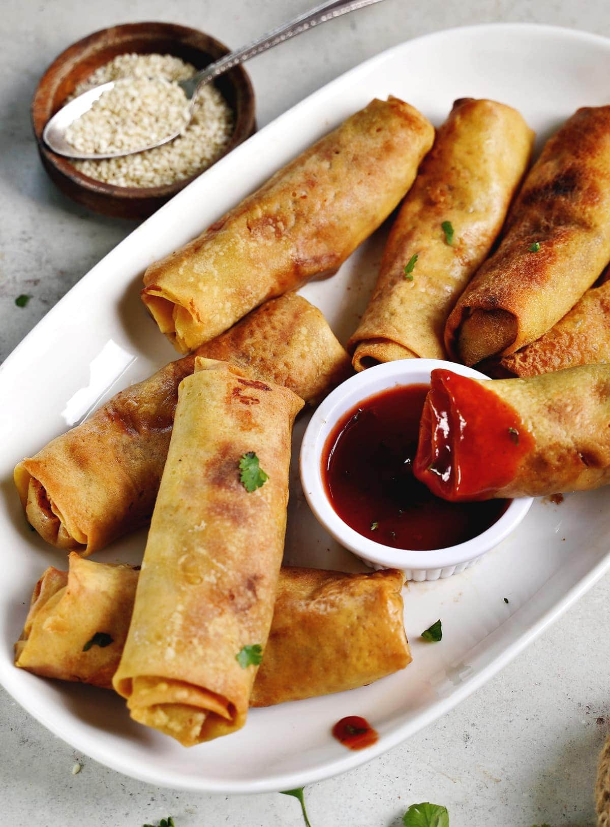 gluten-free spring roll dipped in red sauce on white plate