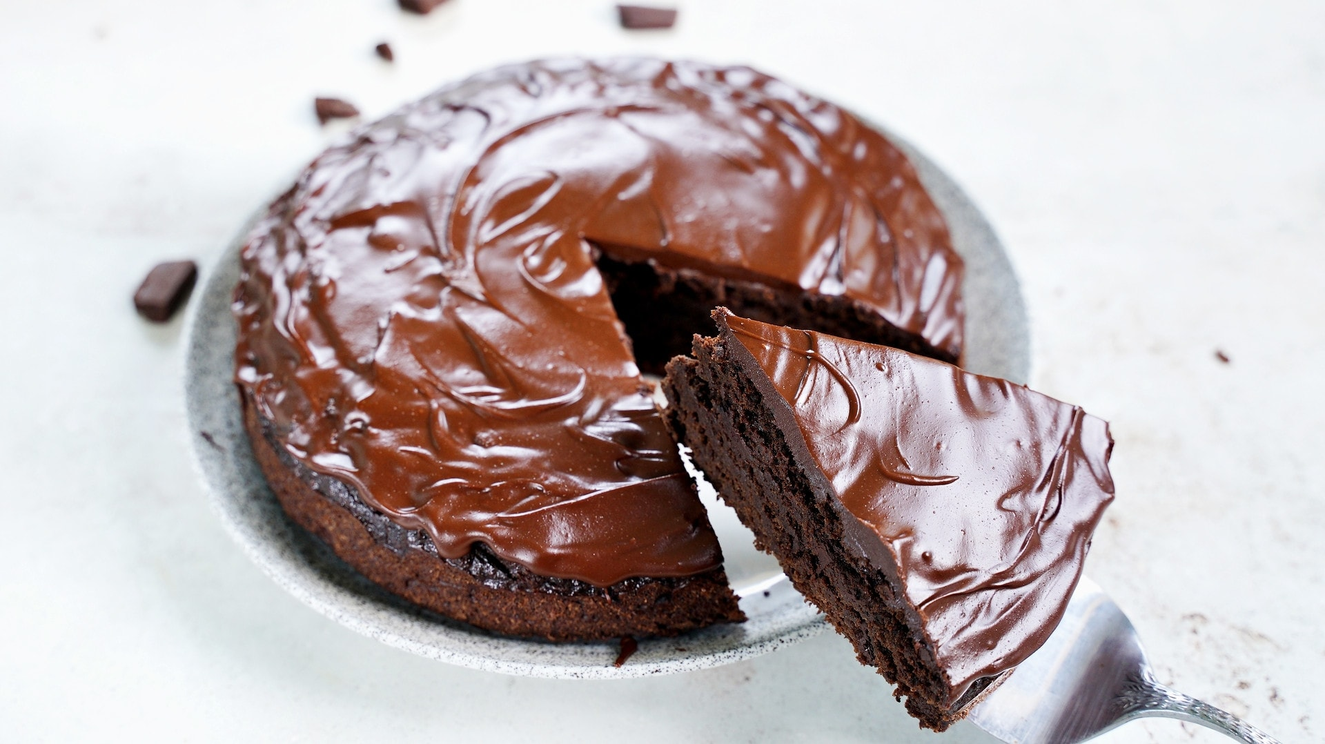 horizontal shot of gluten-free chocolate cake with ganache and a piece cut out