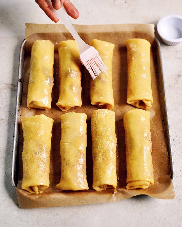 pancake rolls on baking sheet being brushed with oil before baking