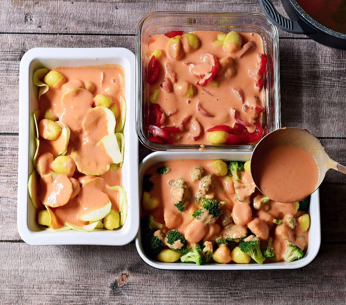 pouring tomato cream sauce in three baking dishes containing gnocchi and veggies