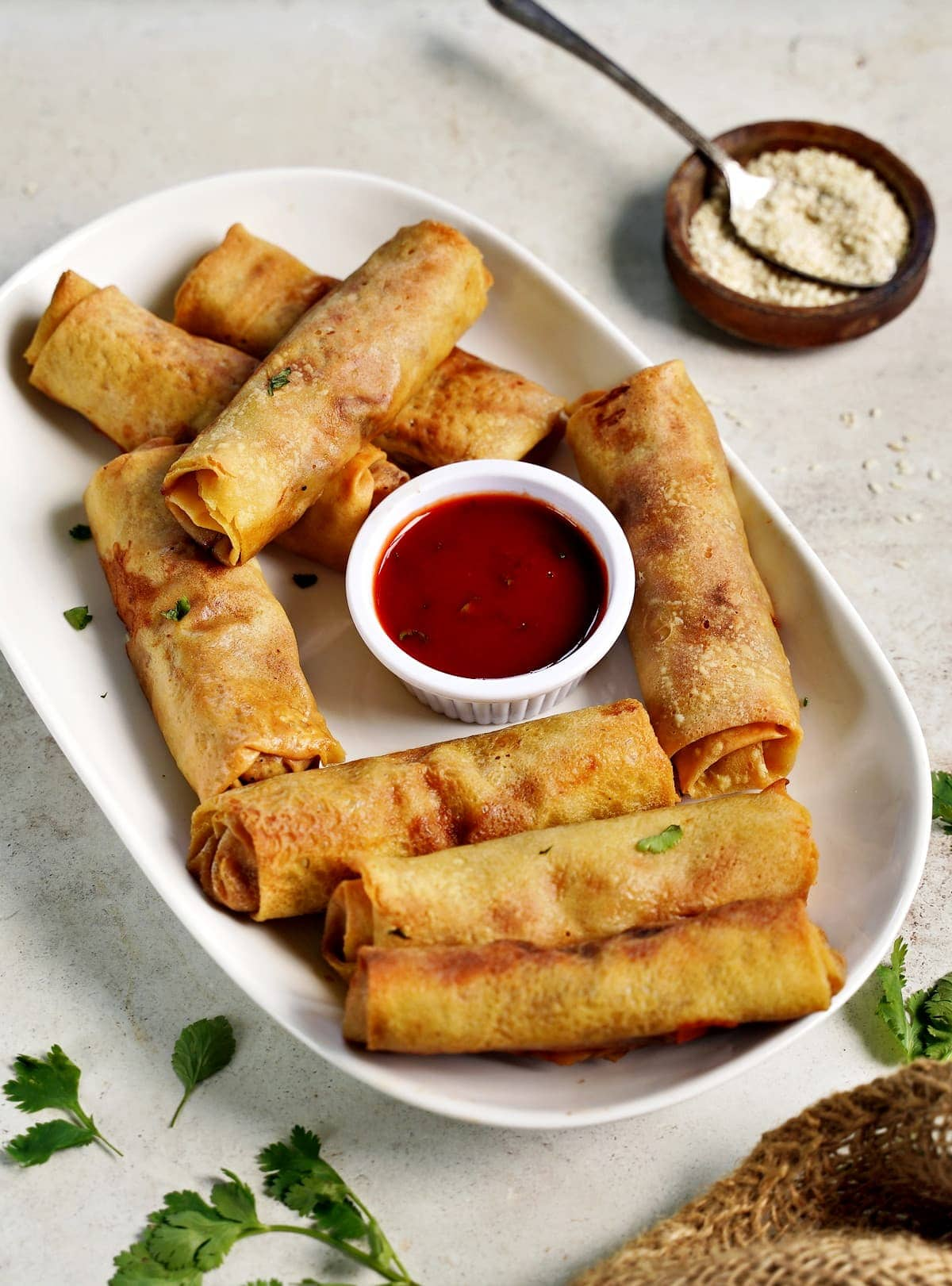 side view of pancake rolls with red sauce on white plate