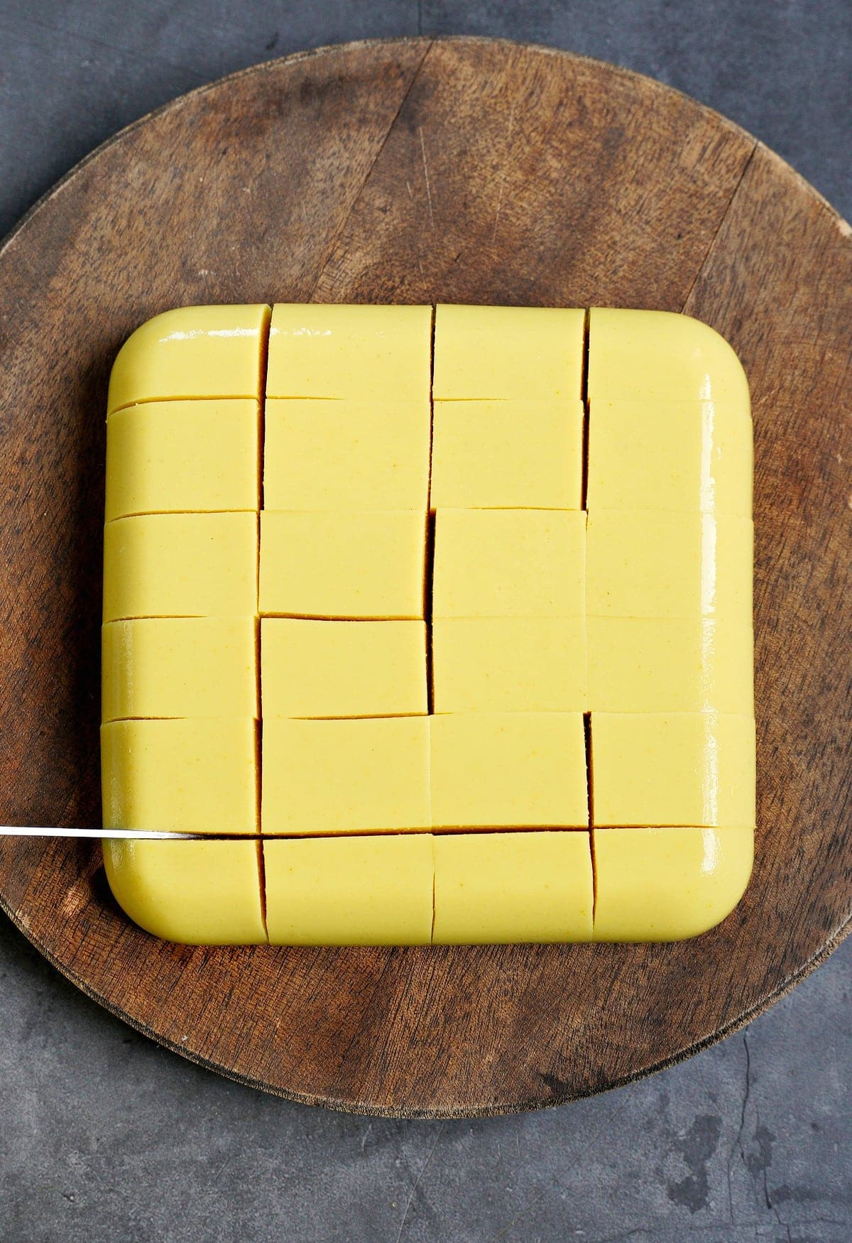 slicing a block of homemade yellow soy-free tofu with a knife on wooden round cutting board