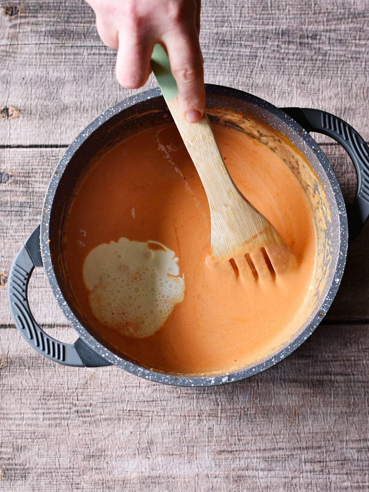 stirring creamy tomato sauce with vegan cream