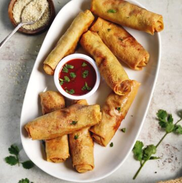top view of baked vegan spring rolls on white plate with red dip