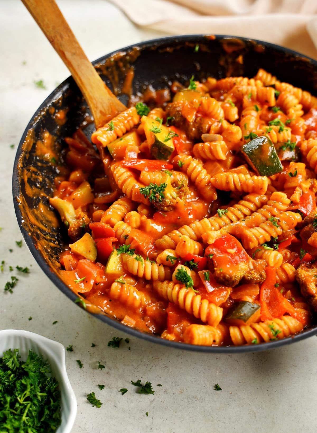 Nahaufnahme von cremiger One-Pot-Pasta in Pfanne mit einem Rührlöffel