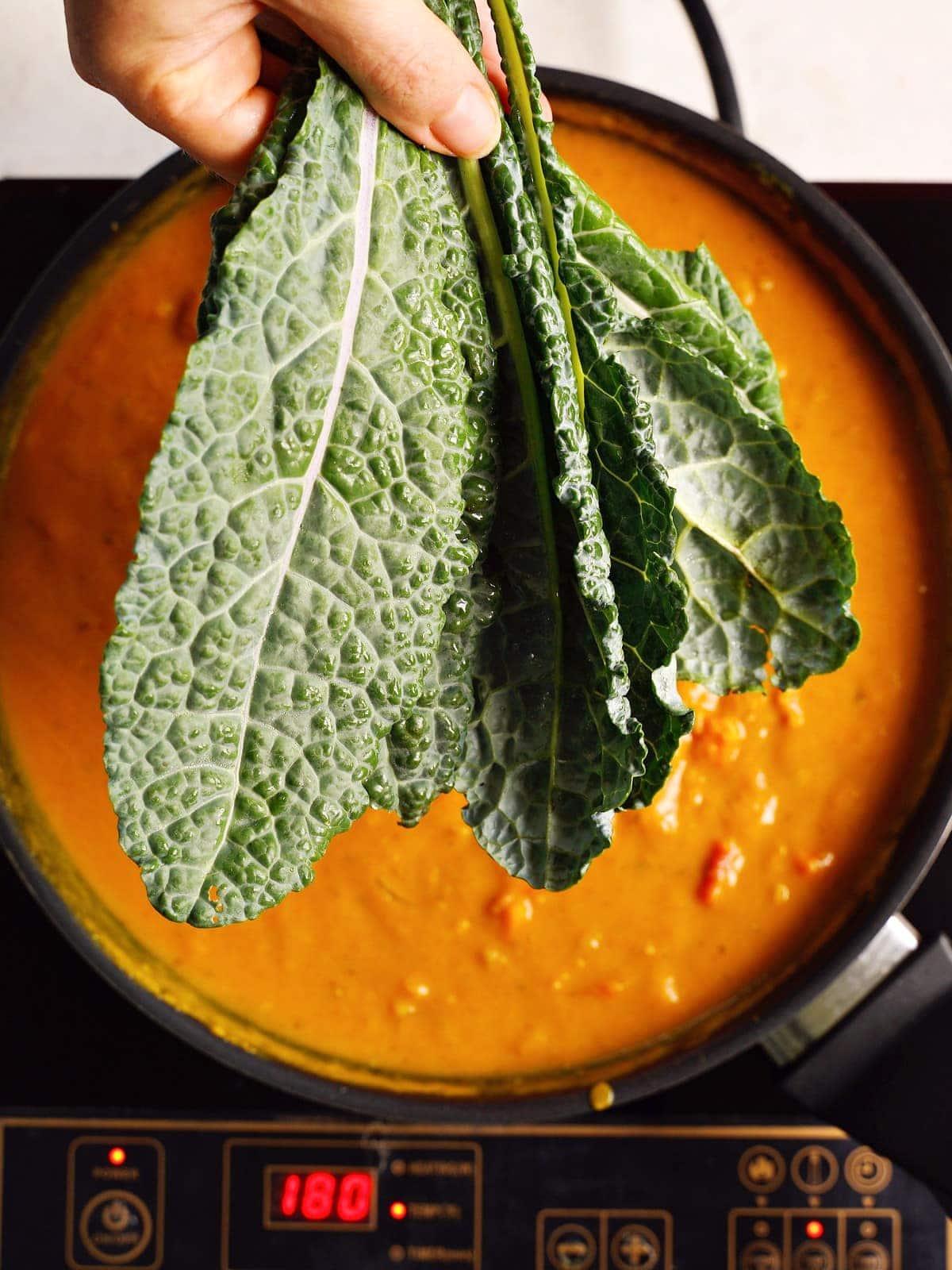 Hand hält Grünkohlblätter über schwarzer Pfanne mit gelbem Curry