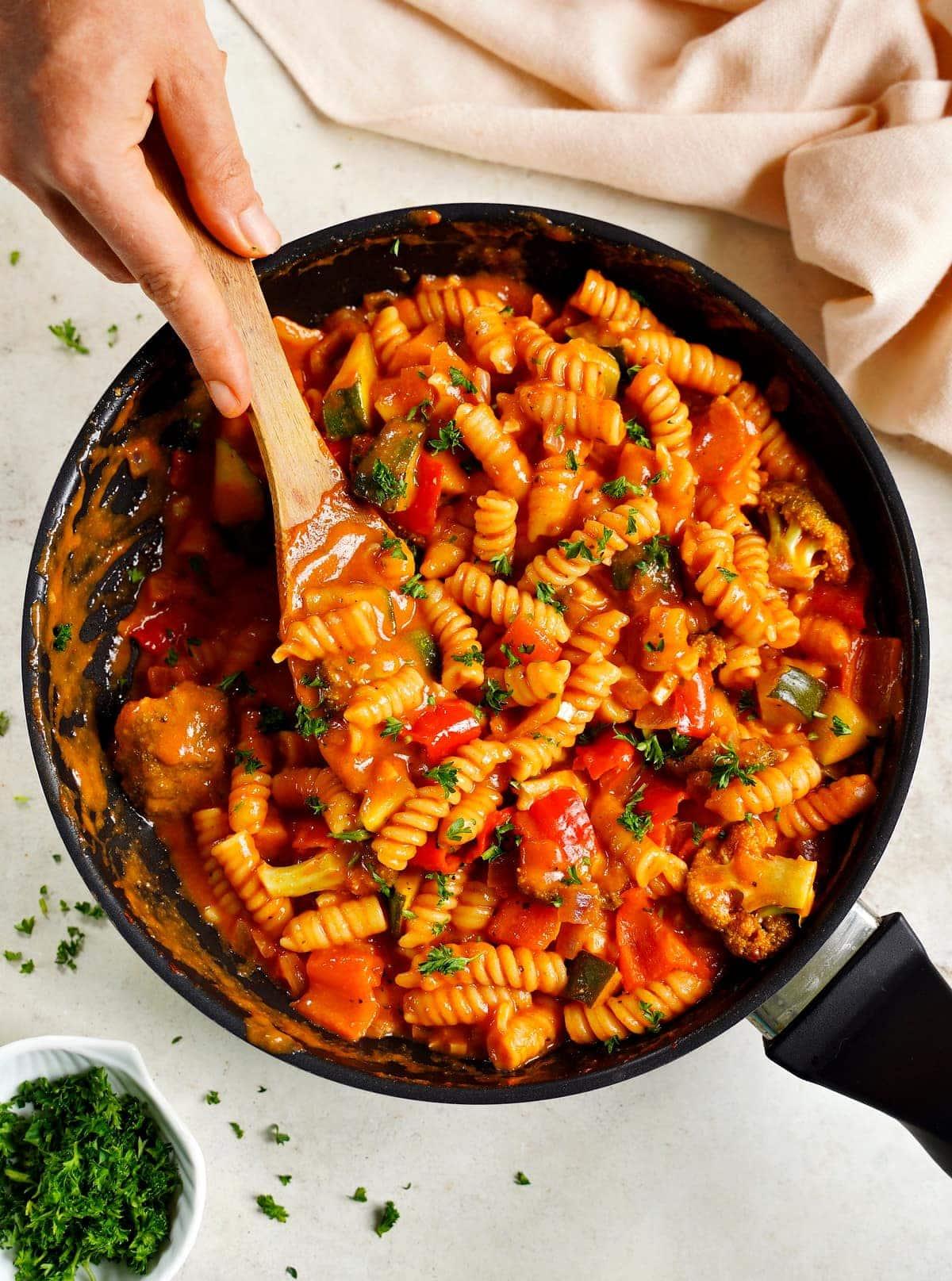 One Pot Pasta mit Gemüse in schwarzer Pfanne mit cremiger Tomatensauce wird mit Holzlöffel gerührt