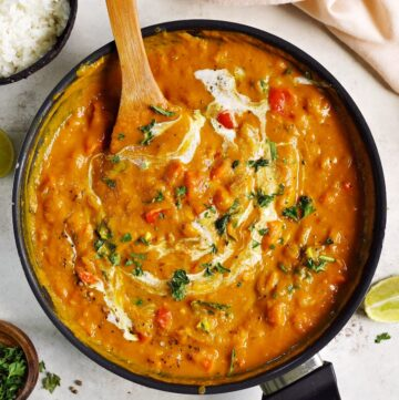one pot pumpkin curry in black skillet with wooden spoon